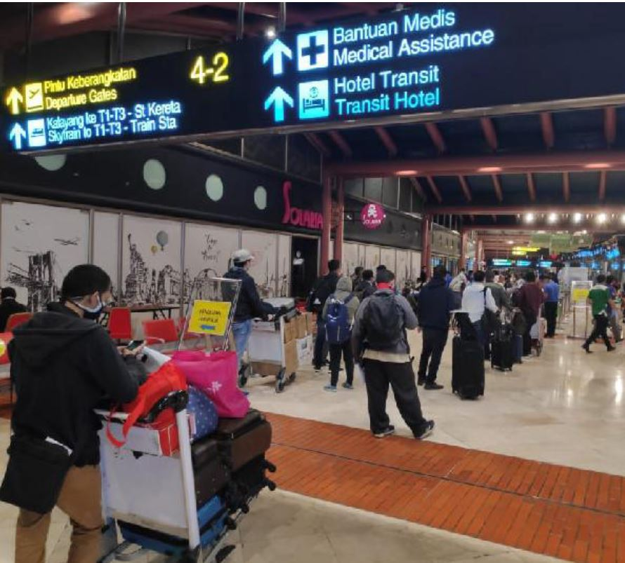 Passengers wait in line at jakarta airport using social distancing