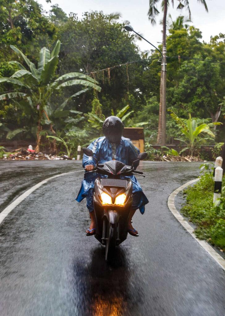 bali local wearing rain jacket on scooter in rain