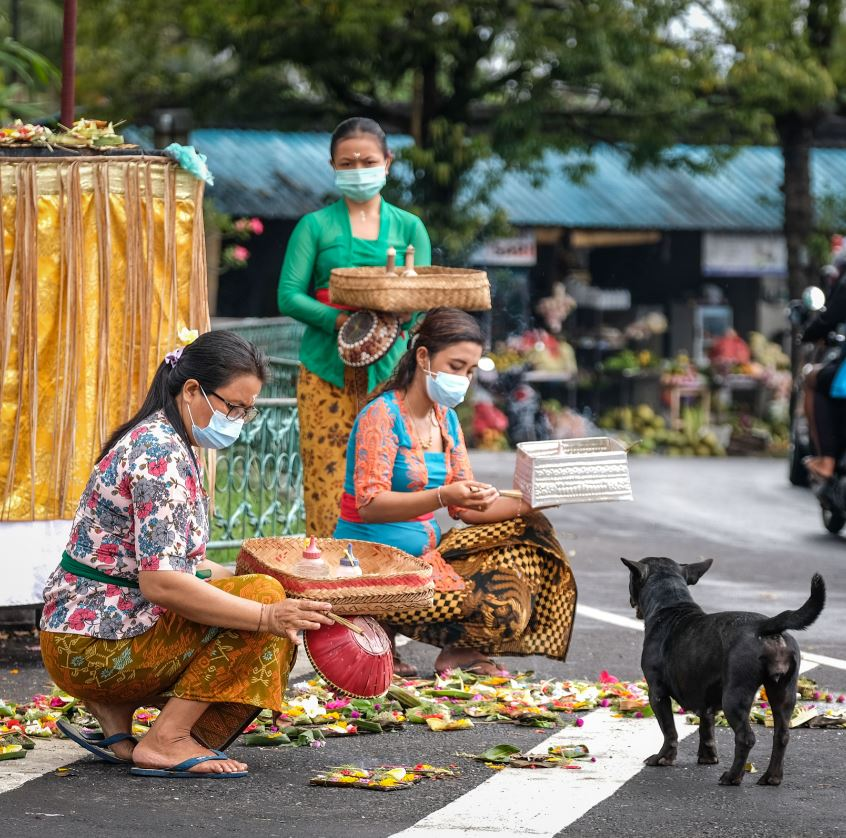 bali locals doing offerings in masks