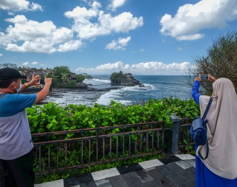 locals taking photos on phones by beach in Bali