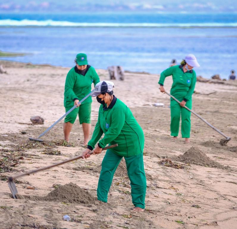 Bali staff cleaning beach