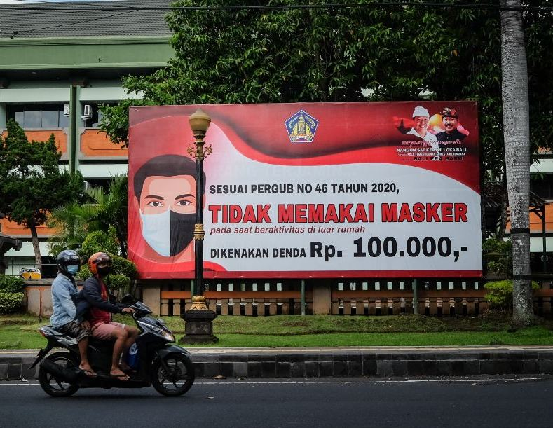 locals in Bali on motorbike infront of Masks covid sign