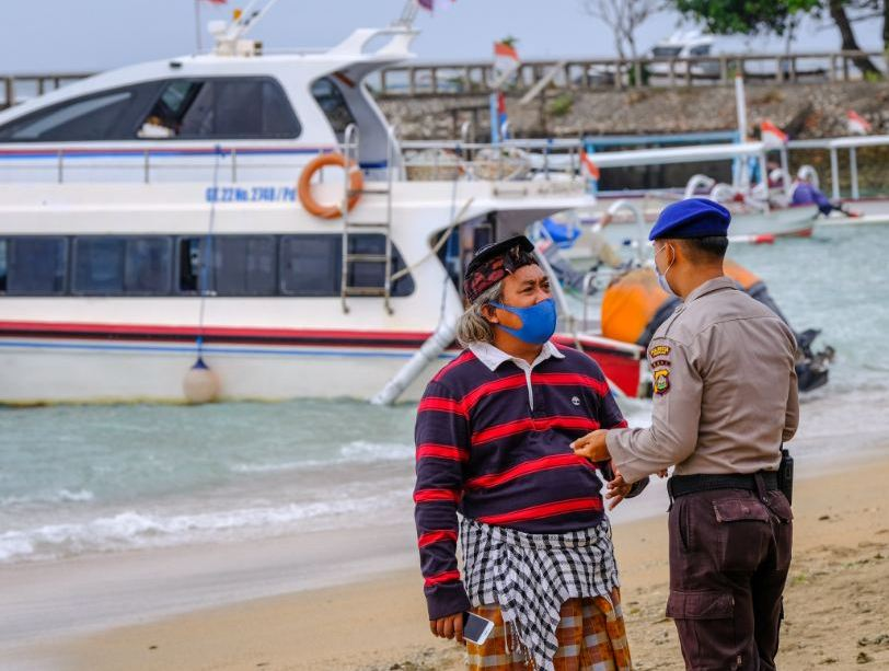 officer investigating local at beach in Bali