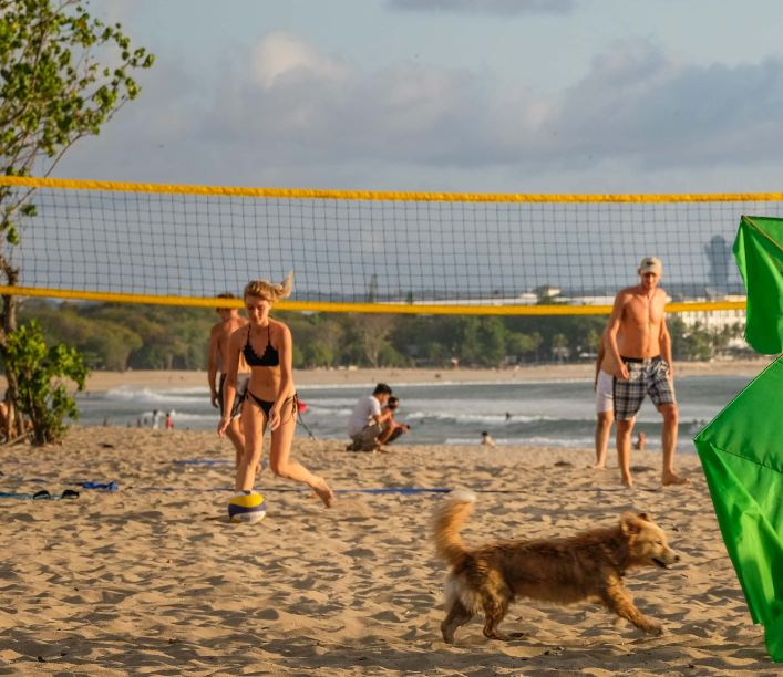 tourists playing volleyball Bali beach