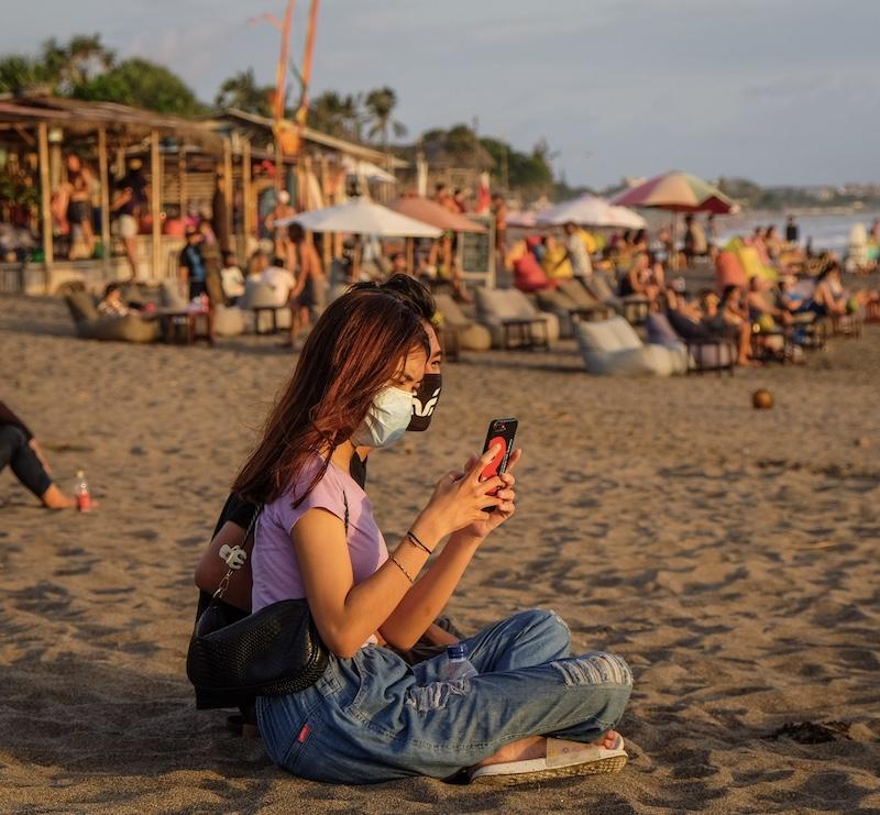 girl mask phone beach