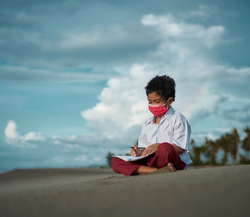 school boy studying on beach bali